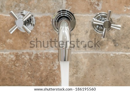 Water pours from a modern faucet. Close-up. - stock photo