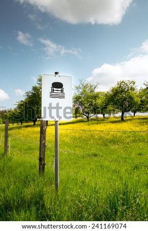 water protection area sign in germany and flower meadow with fruit trees - stock photo