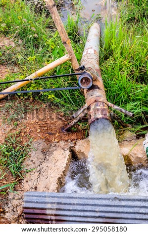Water pump in a tropical culture or field of various food produces in Thailand during the dry season. - stock photo