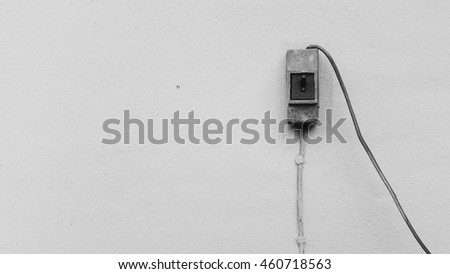 Water pump switch in ON position outside the house's wall with a copy space black and white background