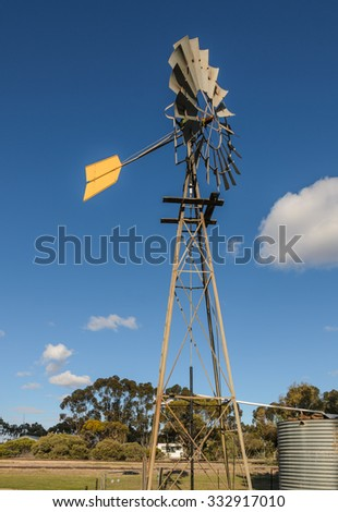 Water pump windmill with a water tank at midday - stock photo