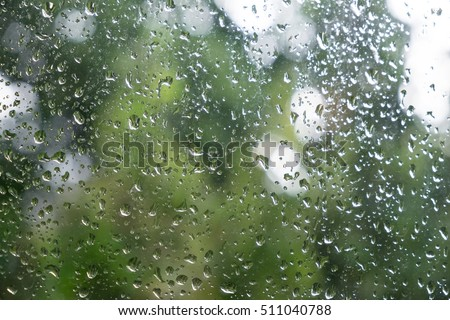 Water rain drop on window glass with relax green leaf view  background.
