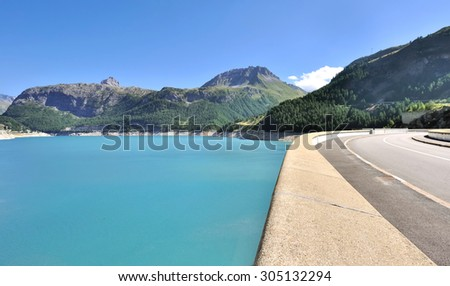water reservoir of a dam bordering a road - stock photo