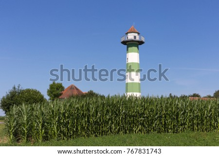 water reservoir tower under blue sky and green field in south germany rural countryside on a hot summer day in july