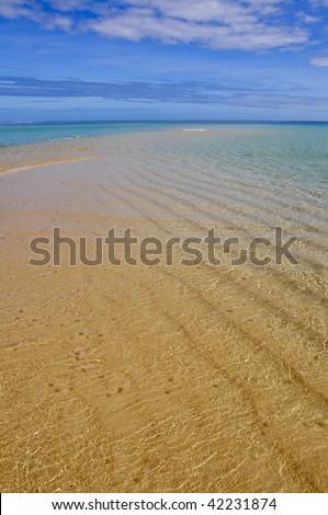 Water rippling on white sandy beach in Fiji - stock photo