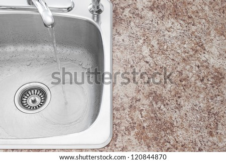 Water running from kitchen faucet. Clean new sink and countertop detail. - stock photo