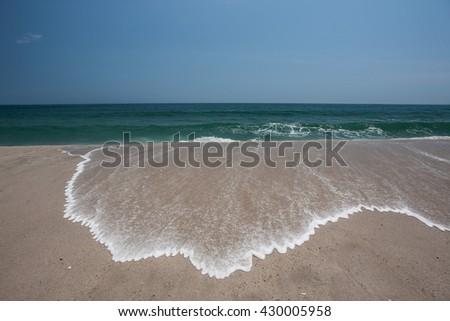 Water runs over a beautiful beach as the tide rises in Cape Cod, Massachusetts.  - stock photo