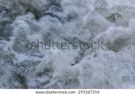 Water rushing and bubbling in a creek or stream with lots of contrasts...fast and slow, hard and soft, dark and light, feather like and pebble like, painterly and sharp. - stock photo