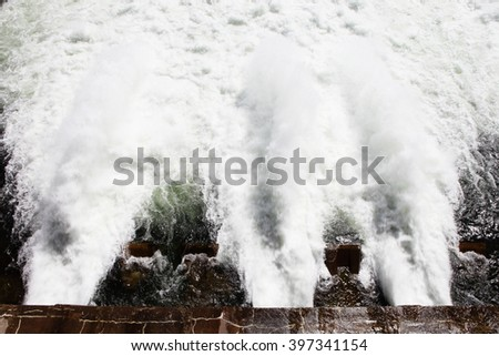 Water rushing through the spillway gates at the dam on Jackson lake in Grand Teton National Park. - stock photo