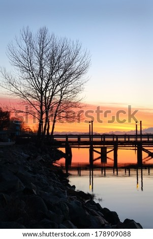 Water's Edge, Fraser River Morning. A fishing pier on the bank of the Fraser River near Steveston at first light. The Cascade Mountain Range is in the background. Richmond, British Columbia, Canada. - stock photo