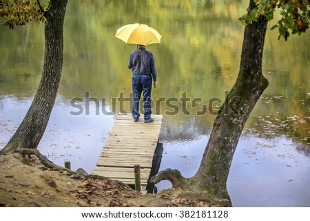 water's edge umbrella man in autumn