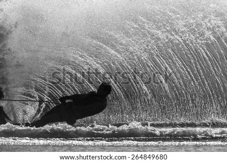 Water Skier Action Black White Water skier hard turn wake of upright water wall spray off ski in black and white vintage. - stock photo