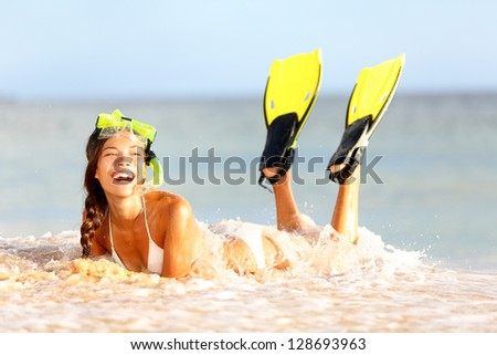 Water snorkeling fun beach woman laughing lying in sand cheerful with fins and mask. Beautiful young multicultural Asian / Caucasian woman.