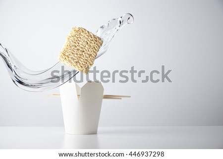 Water splash flies across the brick of dry noodles falls down inside blank takeaway box with chopsticks isolated on white commercial retail set mockup - stock photo