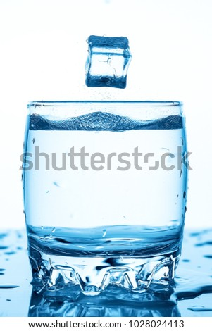 water splash in a glass with a piece of ice on a white background, a piece of ice falling into glass Cup of water,