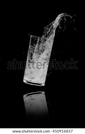 Water splash out of glass on a black background.