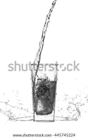 water splash out of glass on black background. - stock photo