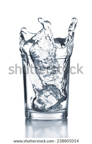 Water splash with ice in glass isolated on white - stock photo