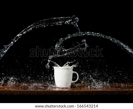 Water splashes in the cup, on black background  - stock photo