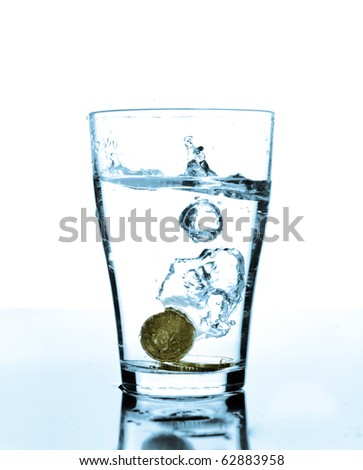Water splashes when a coin dropped in to a glass - stock photo