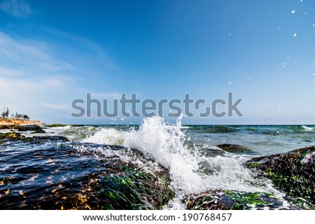 Water splashing. Crystal clear sea water beating against the rocks and cliffs. Blue sky above the beach in the sun zenith refreshing drops of ocean water. Sea waves break on the shore after a storm