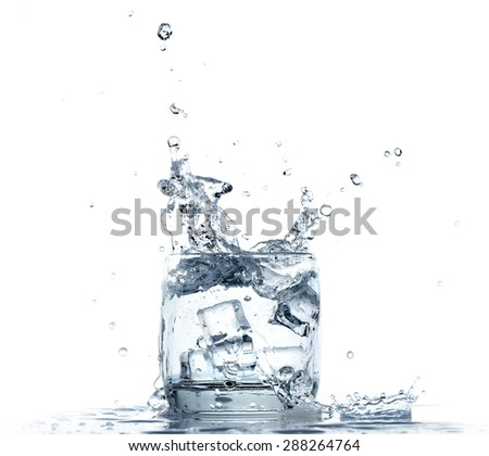 Water splashing from glass on white background - stock photo