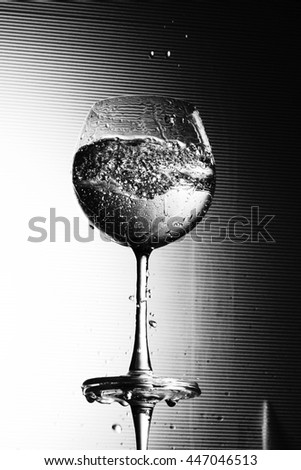 Water splashing in a wineglass in black and white color