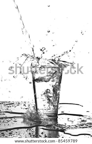 water splashing into a glass on white background - stock photo