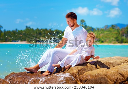 water splashing on happy father and son on tropical beach - stock photo