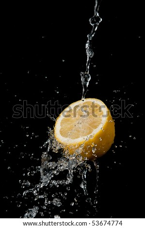 Water splashing on lemon on black background - stock photo