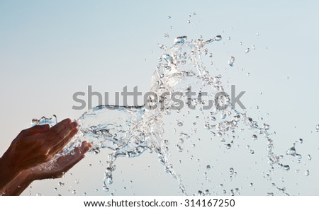 Water splashing out of the hands against the sky - stock photo