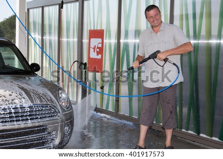 Water spray gun, held by a man, used to wash a car with soap