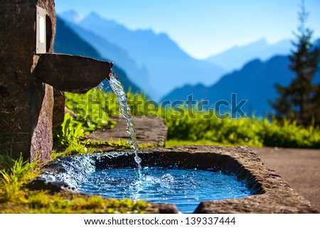 Water spring on Alps mountains background. - stock photo