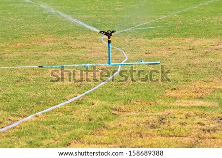 Water springer turning  on the grass around  - stock photo