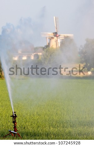 Water sprinkler system irrigating land during a dry summer with a Dutch windmill in the background - stock photo