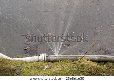 Water sprinkling from a hole in hose - stock photo