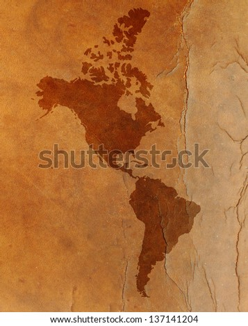 Water stain mark in the shape of the Americas continent map on a vintage brown leather parchment. - stock photo