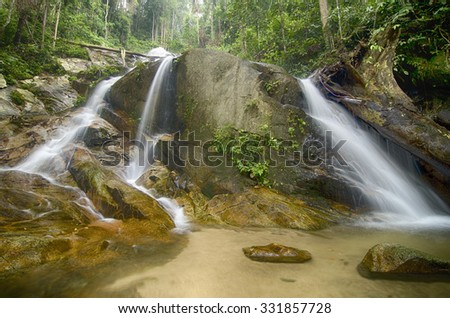 water stream and beautiful waterfall surrounded by green forest clear water and sunlight - stock photo