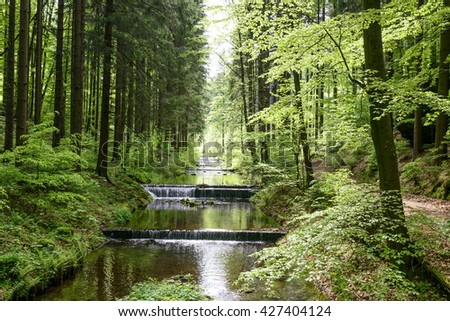 Water stream cascade falls near old gold mine in Zlate Mesto, Czech Republic. Under the cascade falls flock to gold, which later flushed. - stock photo