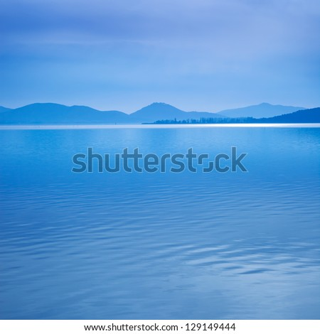 Water surface in a blue morning on the Trasimeno lake, Umbria Italy. Hills on background. Long exposure photography in Lido Camaiore, Versilia, Tuscany, Italy, Europe - stock photo