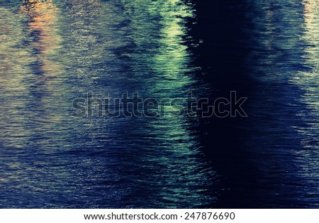 water surface of a town's river at night - stock photo