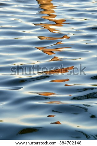 Water surface with ripples and reflections - stock photo