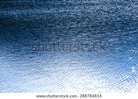 Water surface with ripples and sunrays reflections - stock photo