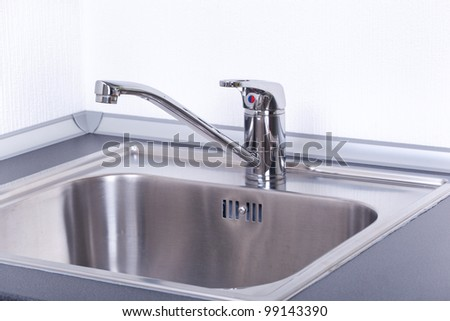 Water tap and sink in a modern kitchen, closeup - stock photo