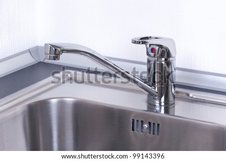 Water tap and sink in a modern kitchen, closeup