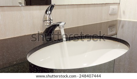 Water tap in the bathroom. Flowing water. - stock photo