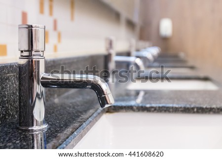 Water tap inside restroom - stock photo