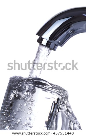 Water tap is pouring overflowing glass isolated on white background - stock photo