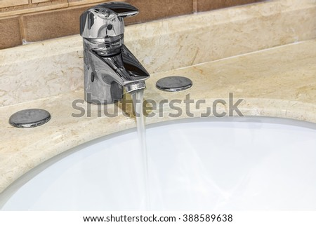 Water tap with a water stream in the bathroom. Focus on handle faucet - stock photo