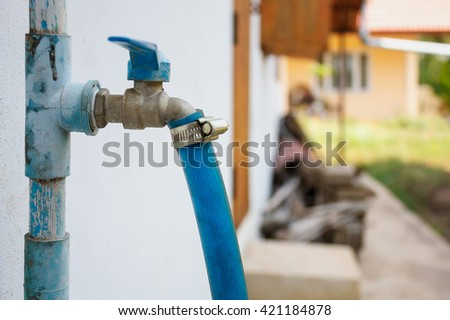 water tap with blue rubber tube